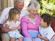Großeltern, die mit Enkelkindern lachen lizenzfreies stockbild