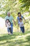 Großeltern, die mit Enkelkindern laufen Stockbild