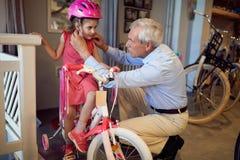 Großeltern, die neues Fahrrad und Sturzhelme für wenig Kind kaufen lizenzfreie stockfotos