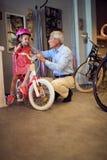 Großeltern, die neues Fahrrad und Sturzhelme für wenig Mädchen kaufen stockfotos