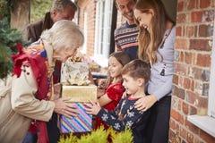 Großeltern, die von der Familie gegrüßt werden, wie sie für Besuch am Weihnachtstag mit Geschenken ankommen stockfotografie