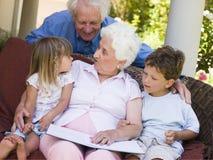 Großeltern, die zu den Enkelkindern lesen Stockfotografie
