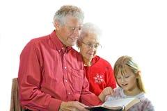 Großeltern, die zum Enkelkind lesen. Lizenzfreies Stockbild