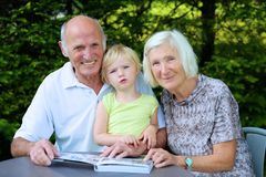 Großeltern mit aufpassendem Fotoalbum des Enkelkindes Stockbilder