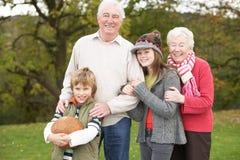 Großeltern mit den Enkelkindern, die Fußball anhalten Lizenzfreie Stockfotos