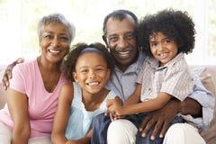 Großeltern mit den Enkelkindern, die sich zu Hause entspannen Lizenzfreies Stockfoto
