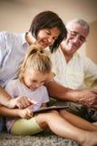 Großeltern mit der Enkelin, die digitales tabl verwendet stockfoto