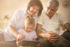 Großeltern mit Enkelin zu Hause stockbilder