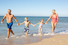 Großeltern mit Enkelkindern auf Strand. stockfotografie