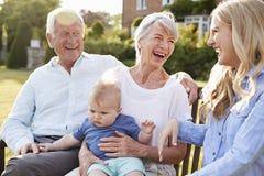Großeltern Sit Outdoors With Baby Grandson und Erwachsen-Tochter lizenzfreie stockfotografie