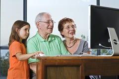Großeltern und Enkelin mit Computer Stockbild