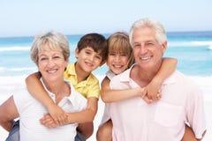 Großeltern und Enkelkinder auf Strand Stockfotografie