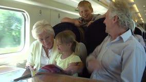 Großeltern und Enkelkinder, die auf Zug-Reise sich entspannen stock video