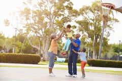 Großeltern und Enkelkinder, die zusammen Basketball spielen Stockbilder
