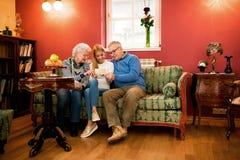 Großeltern und junges Mädchen, die alte Fotos schauen und sprechen Stockbild