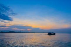 Großer Öltanker und kleines Fischerboot stockbilder