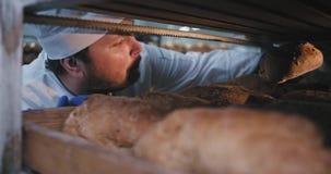 Großer Bäckereimann in einem einheitlichen Innere von industriellen Regalen nehmen ein frisches gebackenes organisches Brot und t stock video