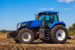 Großer blauer Traktor pflügt das Feld und entfernt die Überreste der vorher gemähten Sonnenblume Stockfotografie