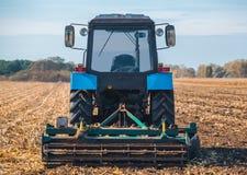 Großer blauer Traktor pflügt das Feld und entfernt die Überreste des vorher gemähten Mais lizenzfreies stockbild