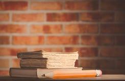 Großer Bleistift und alte Bücher auf Holztisch Stockfotos