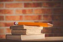 Großer Bleistift und alte Bücher auf Holztisch Lizenzfreies Stockbild