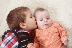 Großer Bruder, der das Baby küsst Stockfotografie