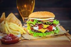 Großer Burger und helles Bier auf einem Holztisch Stockbild