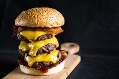 Großer Cheeseburger auf einem dunklen Hintergrund lizenzfreies stockfoto