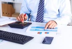 Großer Chef überprüft Berechnungen auf einem Taschenrechner Stockfotografie