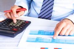 Großer Chef überprüft Berechnungen auf einem Taschenrechner Stockfotos