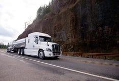 Großer der Anlage LKW-Traktor halb, der halb Anhänger des Behälters auf Gewinn transportiert Stockfotos