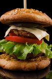 Großer einzelner Cheeseburger lokalisiert auf schwarzem Hintergrund Stockbild