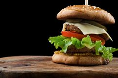 Großer einzelner Cheeseburger lokalisiert auf schwarzem Hintergrund Lizenzfreies Stockfoto