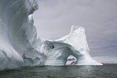 Großer Eisberg mit a durch Bogen in der Antarktis Lizenzfreie Stockfotos