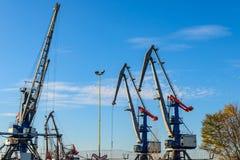 Großer Eisenhafenkran beim Arbeiten an Hintergrund des blauen Himmels stockbilder