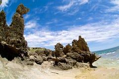Großer Felsen auf dem Strand mit blauen Wolken wie Stockfotografie