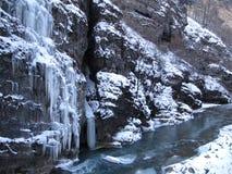 Großer Felsen mit überhängenden Eiszapfen auf den Banken des Gebirgsflusses im Winter stockfotos