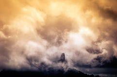 Großer Felsen umgeben durch Wolken bei Sonnenuntergang stockfotos