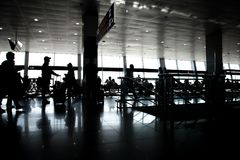 Großer Fensterplatz, der die schwarzen weißen Schattenbildsonnenpassagiere warten Toranschlussflughafen stillsteht stockfoto