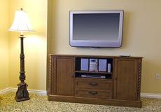 Großer Fernsehapparat über hölzernem Kabinett und Lampe Lizenzfreie Stockbilder
