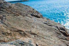 Großer flacher Stein durch das Meer im sonnigen Wetter stockfotografie