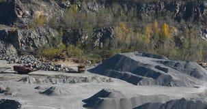 Großer gelber Kipplaster in einem Steinbruch-, Bagger- und Kipplastersteinbruch, industrieller Kipplaster in einem Steinbruch stock footage