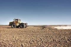 Großer gelber Traktor ausgerüstet mit der Egge, die an dem Feld arbeitet stockfoto