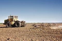Großer gelber Traktor ausgerüstet mit der Egge, die an dem Feld arbeitet lizenzfreie stockfotografie