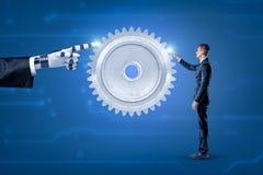 Großer grauer Gang mit einer Roboterhand auf einer Seite und einem Geschäftsmann auf einer anderen Seite auf blauem Hintergrund lizenzfreies stockfoto