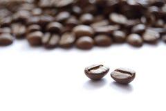 Großer Haufen von den Brown-Kaffeebohnen lokalisiert auf weißem Hintergrund Stockbild