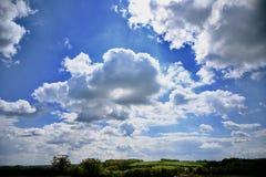 Großer Himmel - Sunny Clouds Over Rural Setting lizenzfreie stockbilder