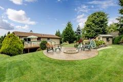 Großer Hinterhof mit Gras, Kreispatio, Stühlen und Garten lizenzfreies stockbild