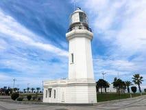Gro?er hoher wei?er Steinleuchtturm auf dem tropisches Seewarmen Sommerurlaubsort mit Palmen gegen den blauen Himmel lizenzfreie stockfotografie