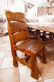 Großer Holzstuhl, der hinter Speisetische steht Stockfotos